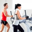 Man and woman with elliptical cross trainer at gym — Stock Photo #8511201