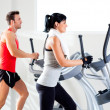 Man and woman with elliptical cross trainer at gym — Stockfoto