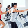 Man and woman with elliptical cross trainer at gym - Stock Photo
