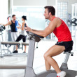 Man on stationary bicycle at sport fitness gym - Stock Photo