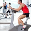 Stock Photo: Man on stationary bicycle at sport fitness gym