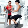 Woman on stationary bicycle with personal trainer — Stock Photo #8511292