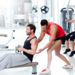 Gym man with personal trainer and fitness woman — Foto de Stock