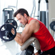 Foto Stock: Man with weight training equipment on sport gym