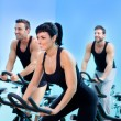Stationary spinning bicycles fitness girl in a gym — Stock Photo #8511381