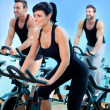 Stationary spinning bicycles fitness girl in a gym — ストック写真