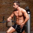 图库照片: Fitness shaped muscle man posing on gym