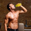Muscle man at gym relaxed with energy drink - Stock Photo
