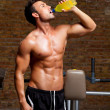 Muscle man at gym relaxed with energy drink — 图库照片