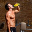 Muscle man at gym relaxed with energy drink — Stockfoto