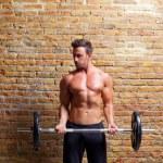 Muskel geformten Körper Mann mit Gewichten auf Ziegelmauer — Stockfoto #8511540