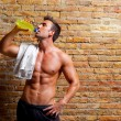 Muscle shaped man at gym relaxed drinking — Стоковая фотография
