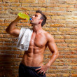 Muscle shaped man at gym relaxed drinking — Photo
