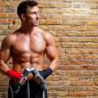 Muscle boxer man with fist bandage and weights - Stock Photo