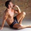 Muscle shaped man sitting relaxed on brickwall - Stock Photo