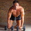 Muscle shaped man on knees with training weights - Stock Photo