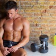 Muscle man relaxed with weights and drink — Stock Photo