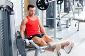 Man lifting weights with a leg press on sport gym — Stock Photo