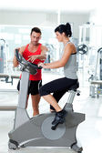 Woman on stationary bicycle with personal trainer — Stock Photo