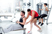 Gym man with personal trainer and fitness woman — Foto Stock
