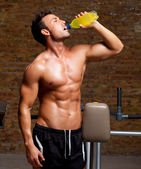 Muscle man at gym relaxed with energy drink — Stock Photo