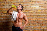 Muscle shaped man at gym relaxed drinking — Stockfoto