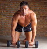 Muscle shaped man on knees with training weights — Stock Photo
