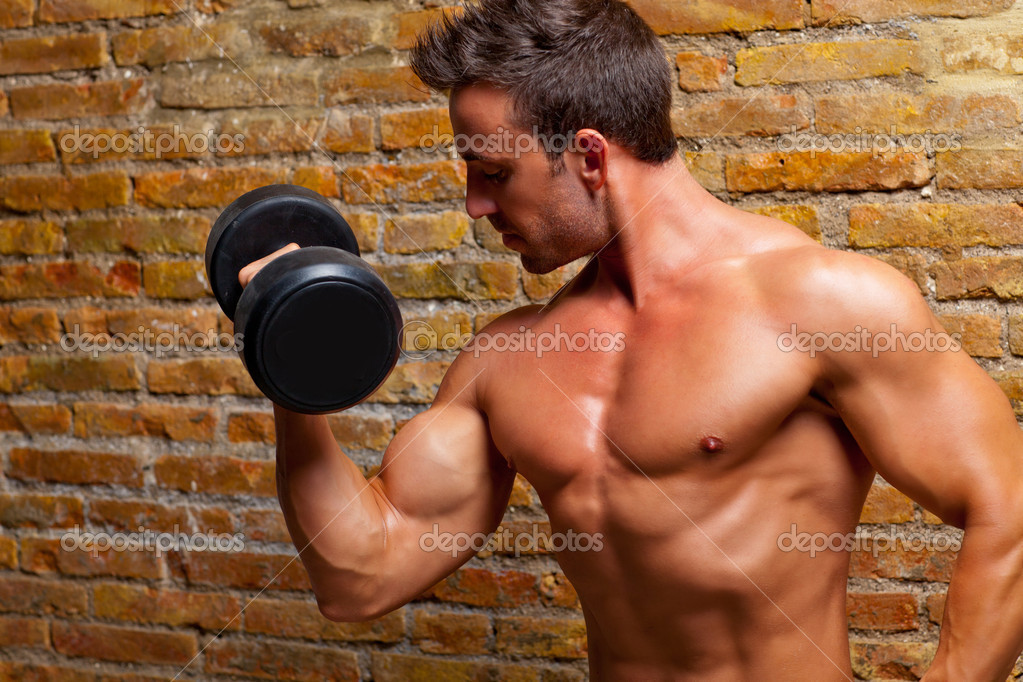 Muscle shaped body man with weights on brick wall gym — Photo #8511666