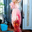 Fashion vintage blond housewife cleaning mop chores - Stock Photo
