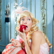 Blond fashion princess eating apple with flowers dress — Stock Photo