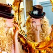 Fashion blond woman with hat in baroque golden mirror - Stock Photo