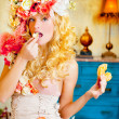 Baroque fashion blonde woman eating dona — Stock Photo #8701700