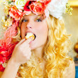 Baroque fashion blonde woman eating dona — Stock Photo