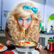 Blonde funny on kitchen eating pasta like crazy — Stock Photo