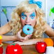 Blonde funny girl on kitchen eating blue dona - Stock Photo