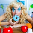 Blonde funny girl on kitchen eating blue dona — Stock Photo