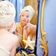 Beauty woman with towel looking at golden mirror — Stock fotografie