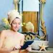 Female in bathroomreading ebook tablet — Stock Photo #8702950