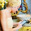 Female in bathroomreading ebook tablet — Stock Photo