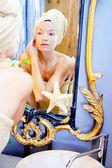 Kobieta uroda ręcznikiem, patrząc na złote lustro — Zdjęcie stockowe