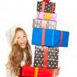 Kid little girl with christmas present gifts stacked — Stockfoto