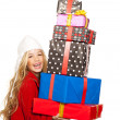 Kid girl holding many gifts stacked on her hand — Stock Photo #8803122
