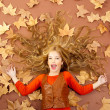 Autumn fall little blond girl on dried tree leaves — Stock Photo #8804644