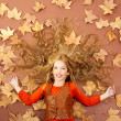 Autumn fall little blond girl on dried tree leaves — Stock Photo #8804770