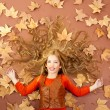Autumn fall little blond girl on dried tree leaves — Stock Photo #8804801