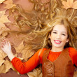 Autumn fall little blond girl on dried tree leaves — Stock Photo #8804853