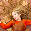 Autumn fall little blond girl on dried tree leaves — Stock Photo #8804955