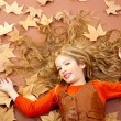 Autumn fall little blond girl on dried tree leaves — Stock Photo #8805008
