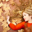 Autumn fall little blond girl on dried tree leaves — Stock fotografie