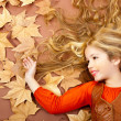 Autumn fall little blond girl on dried tree leaves — Stock Photo #8805171